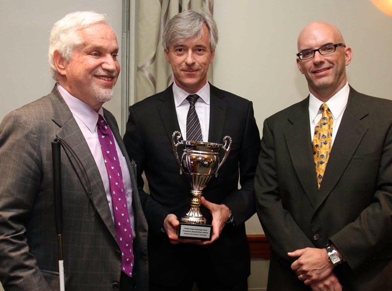"NEMPA members Paul Parravano, left, Co-Director of MIT's Office of Government and Community Relations, and Craig Fitzgerald, Editorial Director of IMN, Inc., flank John Krafcik, CEO of Hyundai Motor America. Krafcik, an MIT alumnus, holds NEMPA's Silver Anniversary Executive Award, presented to him for ""his strong ties to New England as a Connecticut native, MIT Sloan School graduate, and for his sterling success in the automotive industry."" Krafcik also accepted The Yankee Cup Technology Award for his company's Gasoline Direct Injection system."