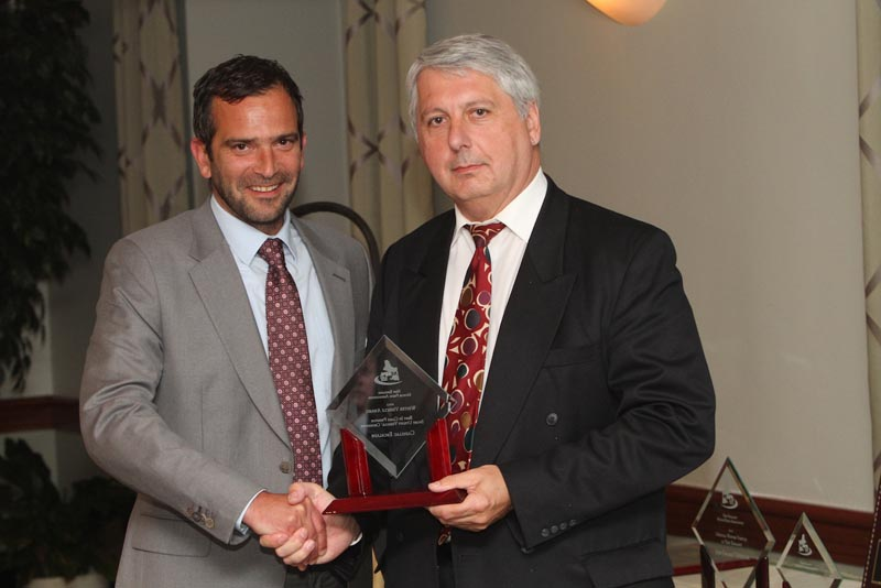 "NEMPA V-P John Paul, right, presents THE CAMEL'S BACK AWARD to Pierre Kanter, President of FMI. This award gets its name from NEMPA's penchant for often untimely and burdensome requests that could be the proverbial ""straw that broke the camel's back""—but that Pierre Kanter has cheerfully fulfilled time and again in his automotive career. Pierre also accepted NEMPA's FAVORITE CONVERTIBLE $35,000-$50,000 AWARD for the Chevrolet Camaro SS. Many NEMPA members regard this Camaro as a contemporary interpretation of a classic design—and it has one of the best exhaust notes on the road. With up to 426 horsepower on tap and excellent handling, comfortable seats and other amenities, the Camaro SS puts Chevrolet back in the pony-car game in a big way."