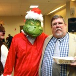 The Grinch checks NEMPA President Keith Griffin's plate while Rudolf flies cover.